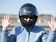 Девушка в мотоциклетном шлеме с поднятыми руками