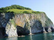 Красивая скала с зеленой лужайкой