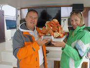 Блюдо с камчатским крабом в руках у мужчины и женщины