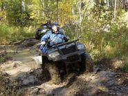Квадрациклист на грязной дороге в лесу