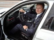 Человек в костюме за рулем белой машины