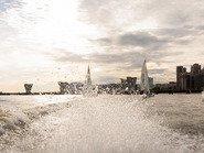 Брызги в воде от мотора на фоне парусных яхт