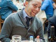 Улыбающийся молодой человек за столом
