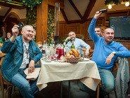 Мужчины за столом с поднятыми айфонами в руках